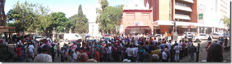 A panoramic view of the gathered crowd listening to a committee member on sound equipment