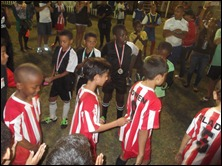 Soccer Kids Academy going forward to receive their winners' medals applauded by the Pirates players