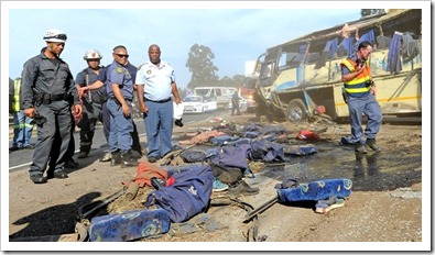 Emergency personnel look at school bags and debris scattered across the N3 northbound after a bus carrying 46 pupils and four staff from Michaelhouse crashed on Tuesday afternoon. (Ian Carbutt)