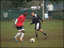 Ayanda Mdlalose (DCLFA) and Kaydon Adonis (M.D.F.A.) compete for the ball